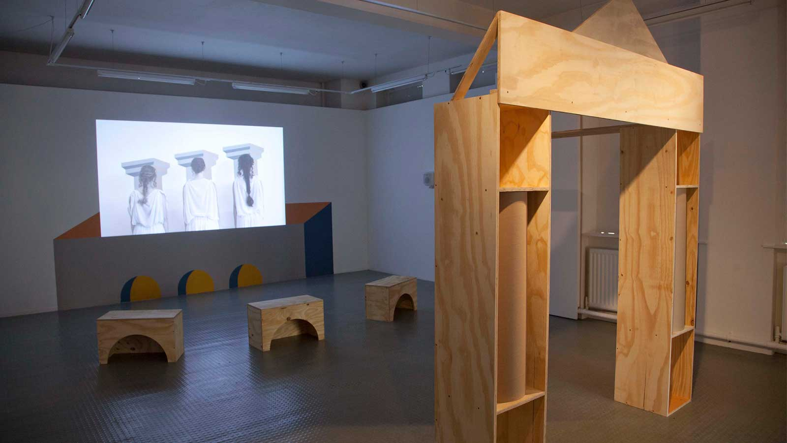 A photograph of Emily Speed's exhibition featuring a gateway made of wooden building blocks and a screen showing a film.