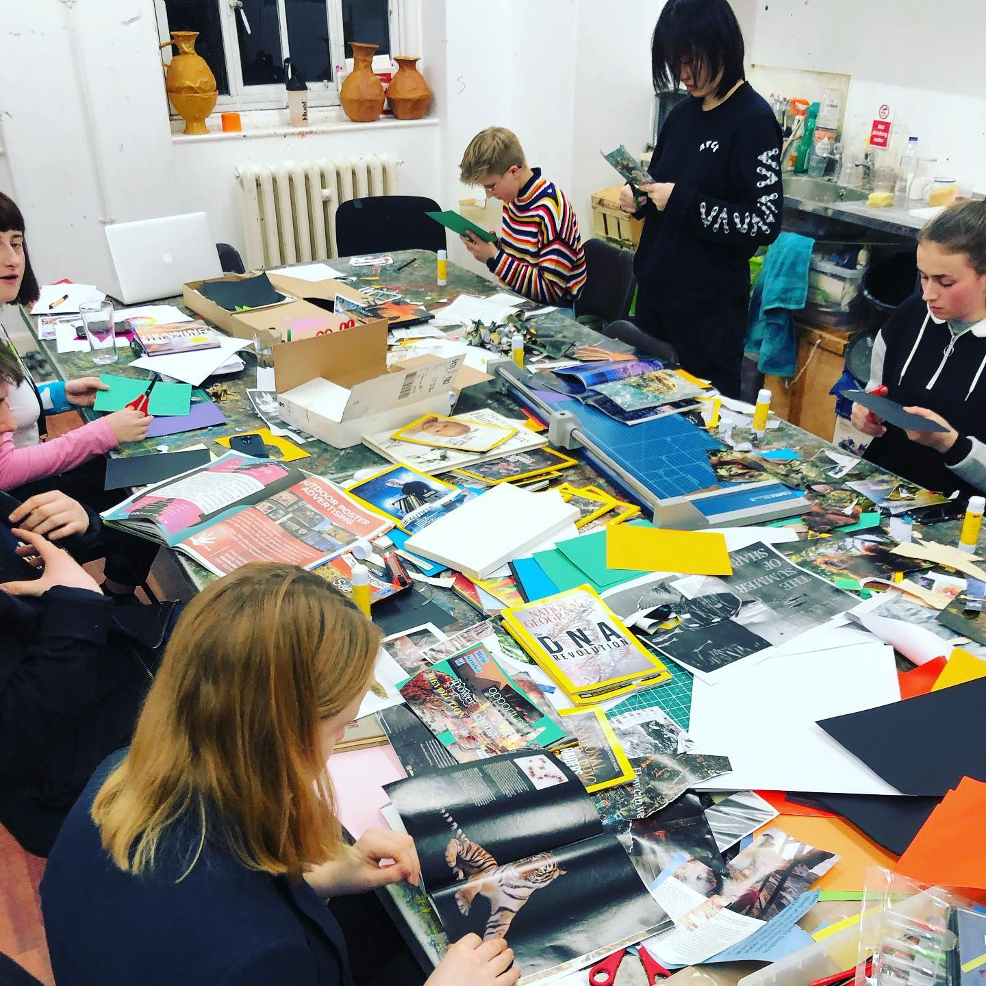 A group of young people are cutting up paper on a messy art table.