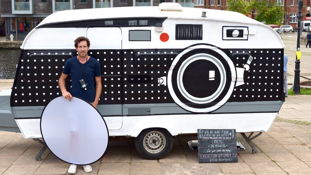 Photographer Brendan Barry stands in front of a giant camera amde out of a caravan