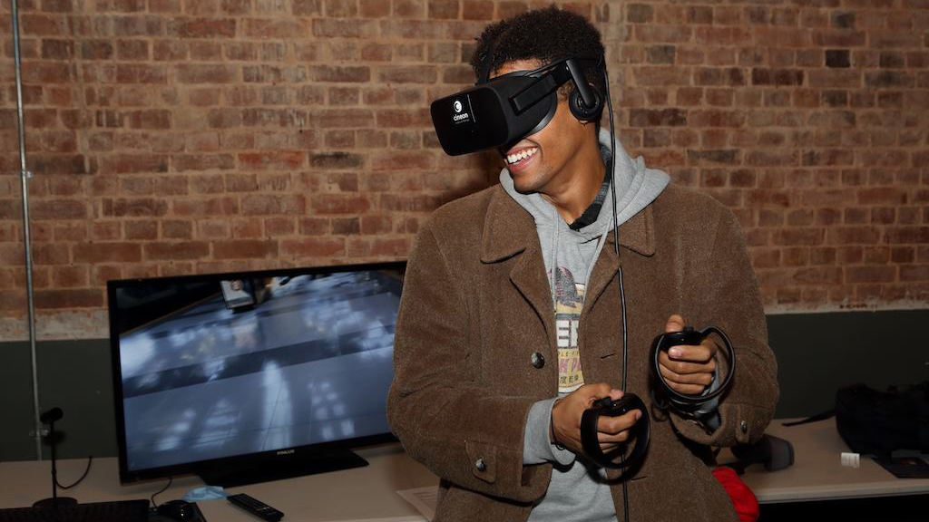 A man smiling and wearing virtual reality headset