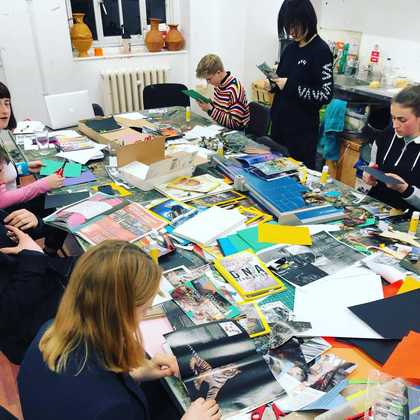 Several young people sitting around a table cutting up magazines and flyers to make a collage