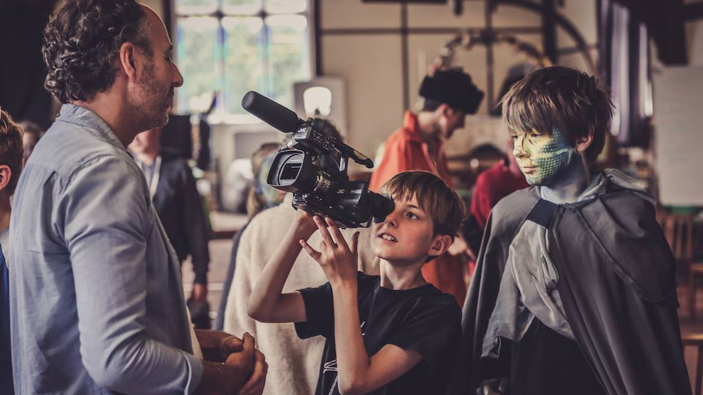 A young boy points a film camera at the teacher at Summer Film School