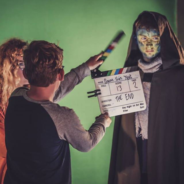 A boy stands in front of a green screen with a filmmakers clapperboard