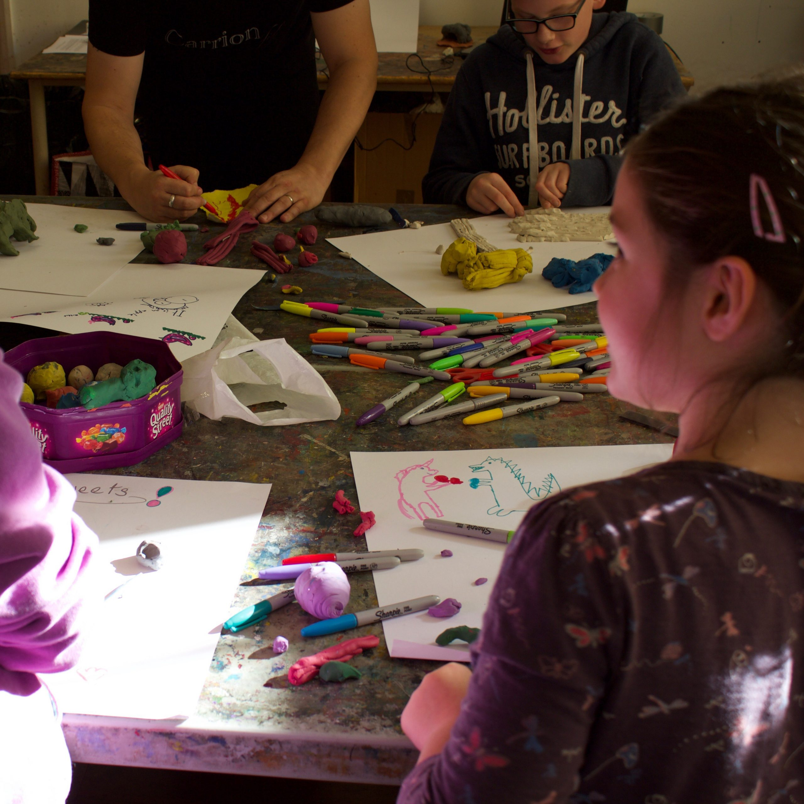 A group of young people make plasticine models