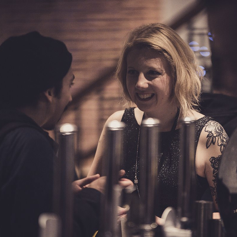 An image of a woman ordering a drink at the bar