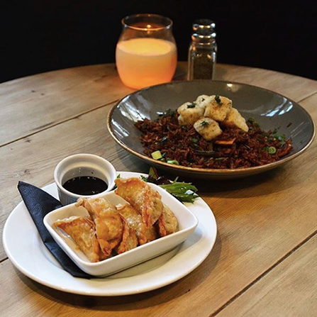 A photograph of vegetable gyoza and a tofu fried rice dish on a wooden table