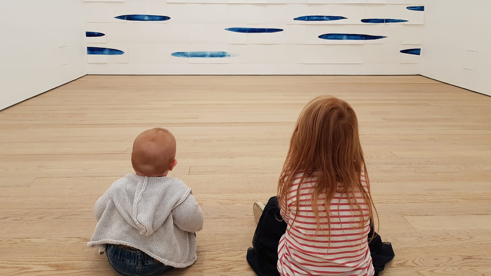 photo of two young girls sat on the floor of the gallery looking at artwork on the wall