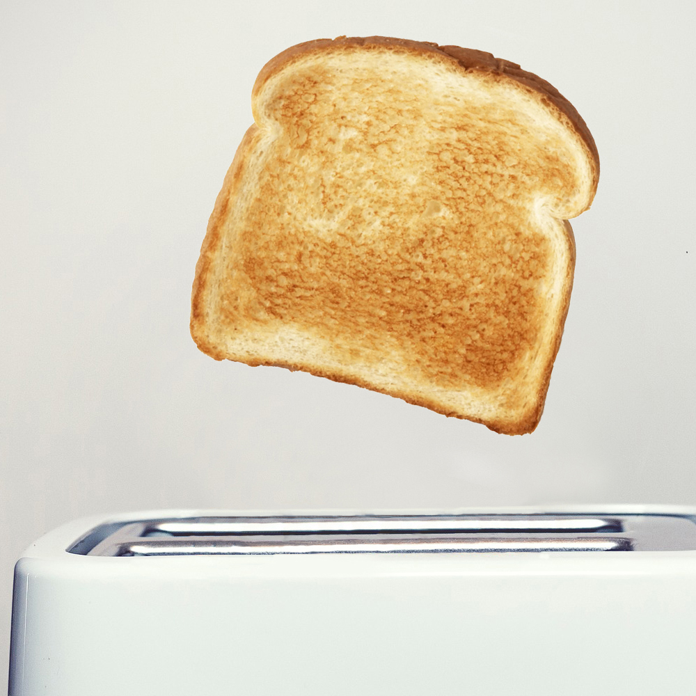 Photograph of toast popping out a toaster