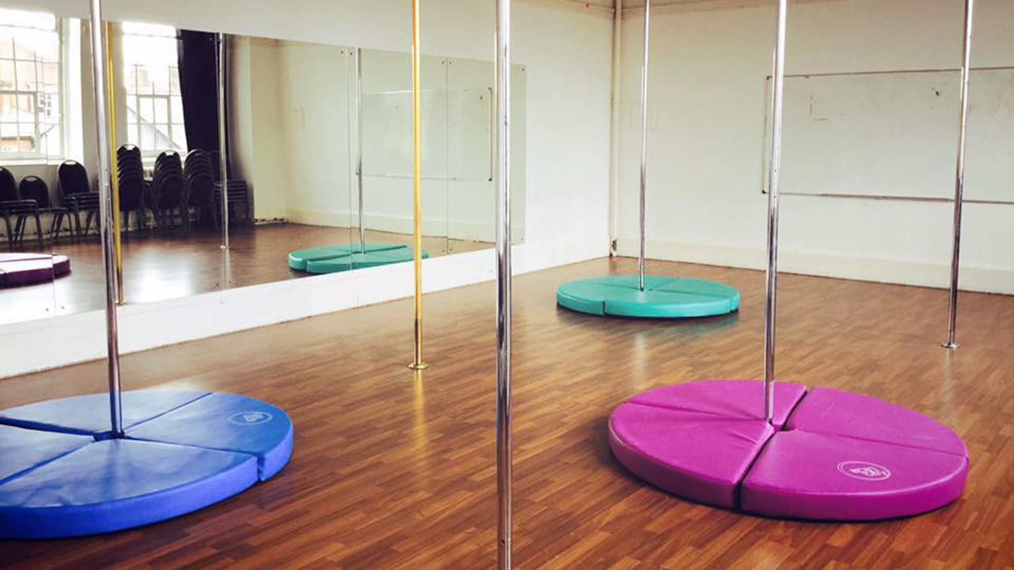 A dance studio with a mirrored wall and spin poles