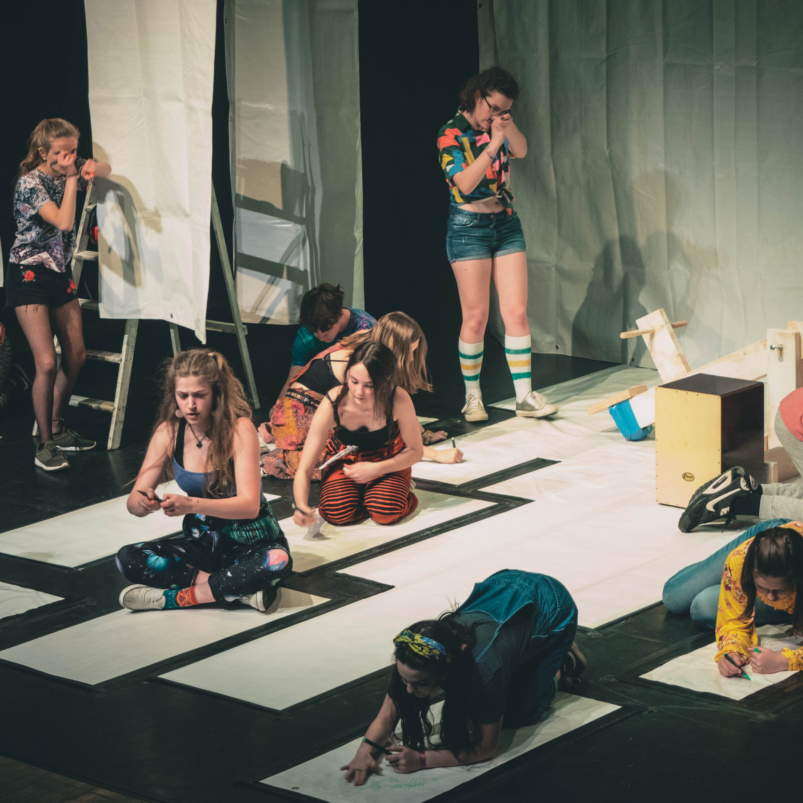 Photo of several young people taking part in a theatre show, many of them are drawing on large pieces of paper