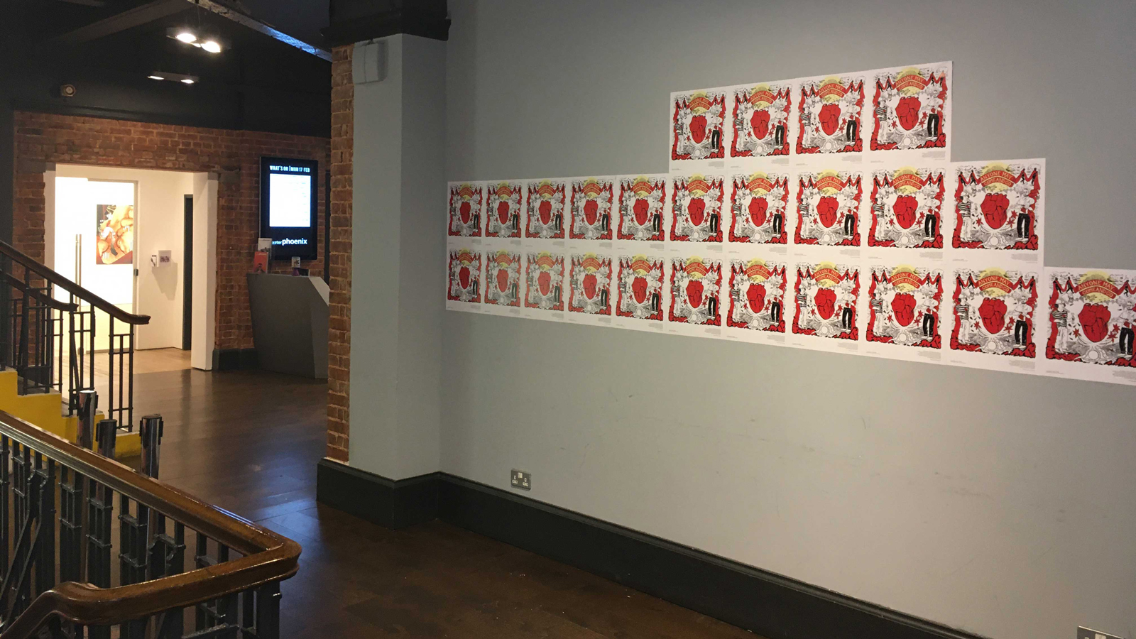 An exhibtion featuring red posters on a grey wall