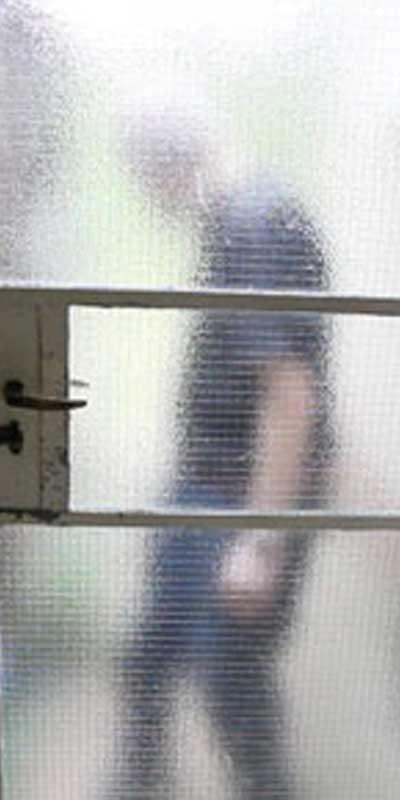 A man's silhouette behind a blurry glass door.