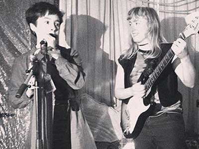 A photograph of someone playing a guitar while someone else speaks into a microphone.