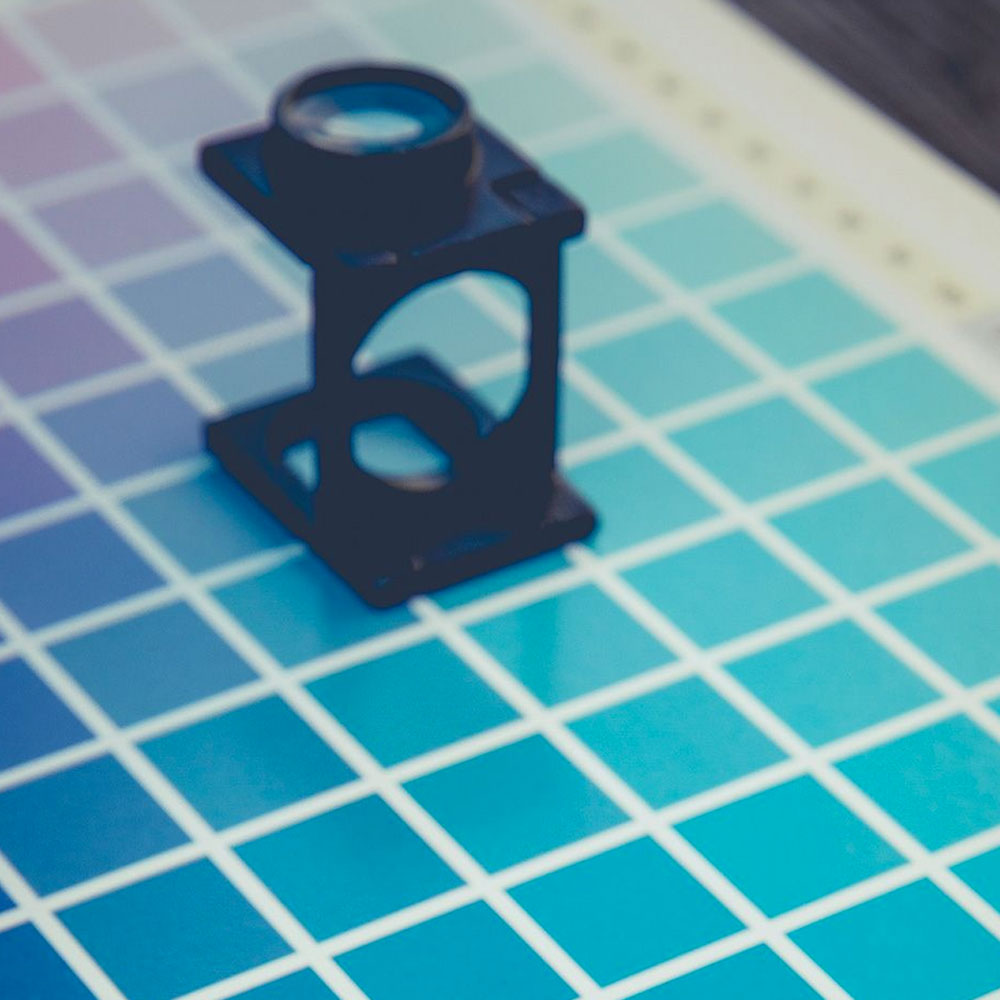 An eyepiece sits ontop of a graphic designer colour chart.