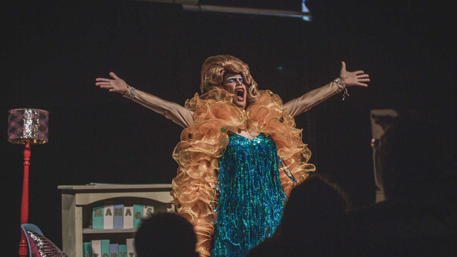 Drag queen Mama G performs in Studio 1 in a blue sequinned dress and orange feather boa