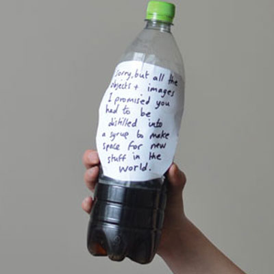 A hand holds up a plastic bottle half filled with syrup.