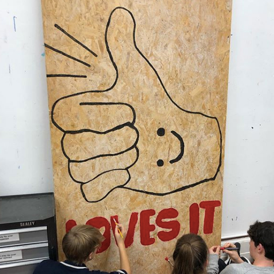 Members of youth group Freefall paint a large scale thumbs up with a smily face in the palm
