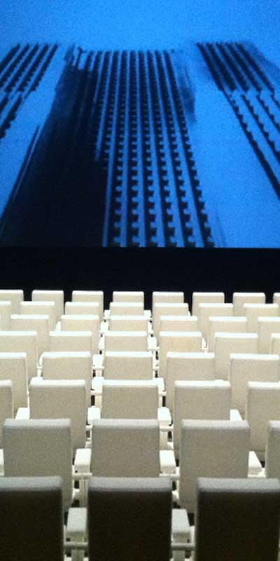 A still from Maia Conran's digital work 'Crowd' featuring rows of empty chairs.