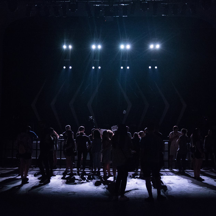 Dancers stand on a dark stage, back lit with spotlights