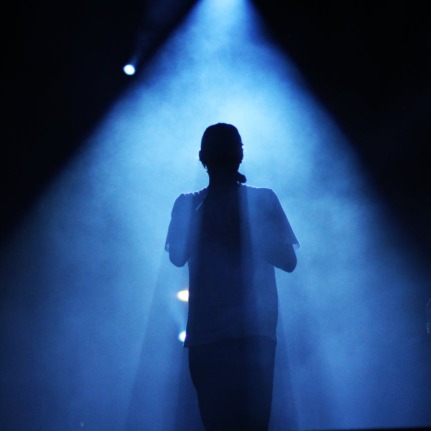 A performer stands on stage backlit with a blue light
