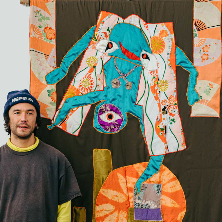Artist Huhtamaki Wab stands besides one of his tapestries.