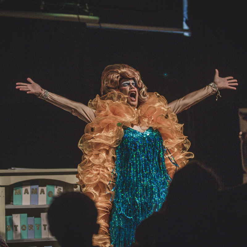 Drag performer mama g takes to the stage in a feather boa and sequinned gown