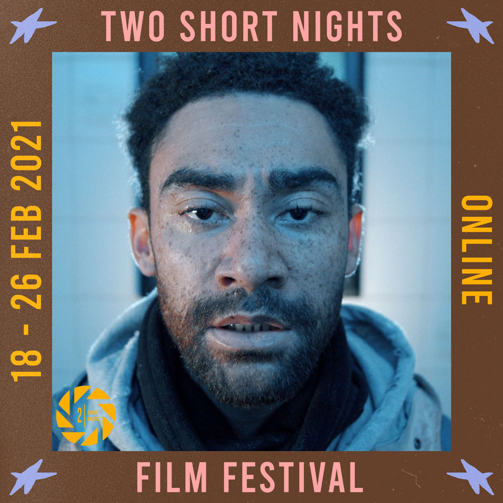 A close up of still from a film sees a mean looking directly at the camera in close up. Words read Two Short nights Online Film Festival