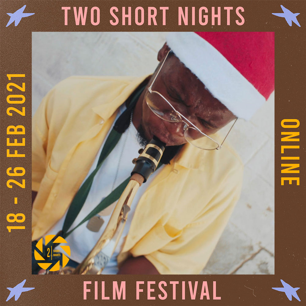 A man in a yellow short sleeved shirt and santa hat plays a saxophone. The image is framed by a border with the words that read Two Short Nights Online Film Festival