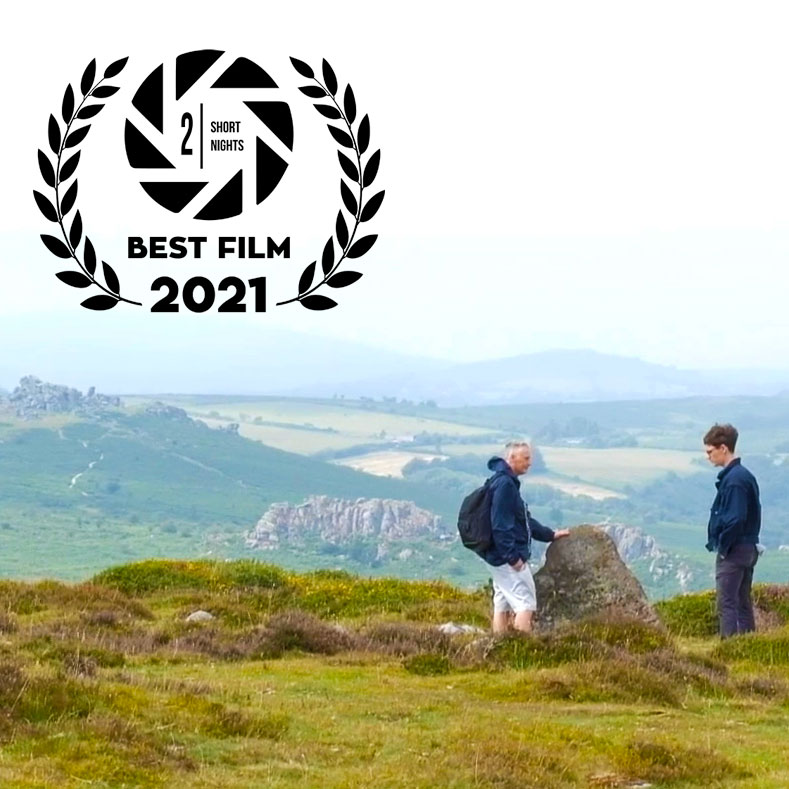 An image of a young man talking to his dad atop a hill in Dartmoor. A laurel at the top left of the image reads 2 Short Nights Best Film 2021