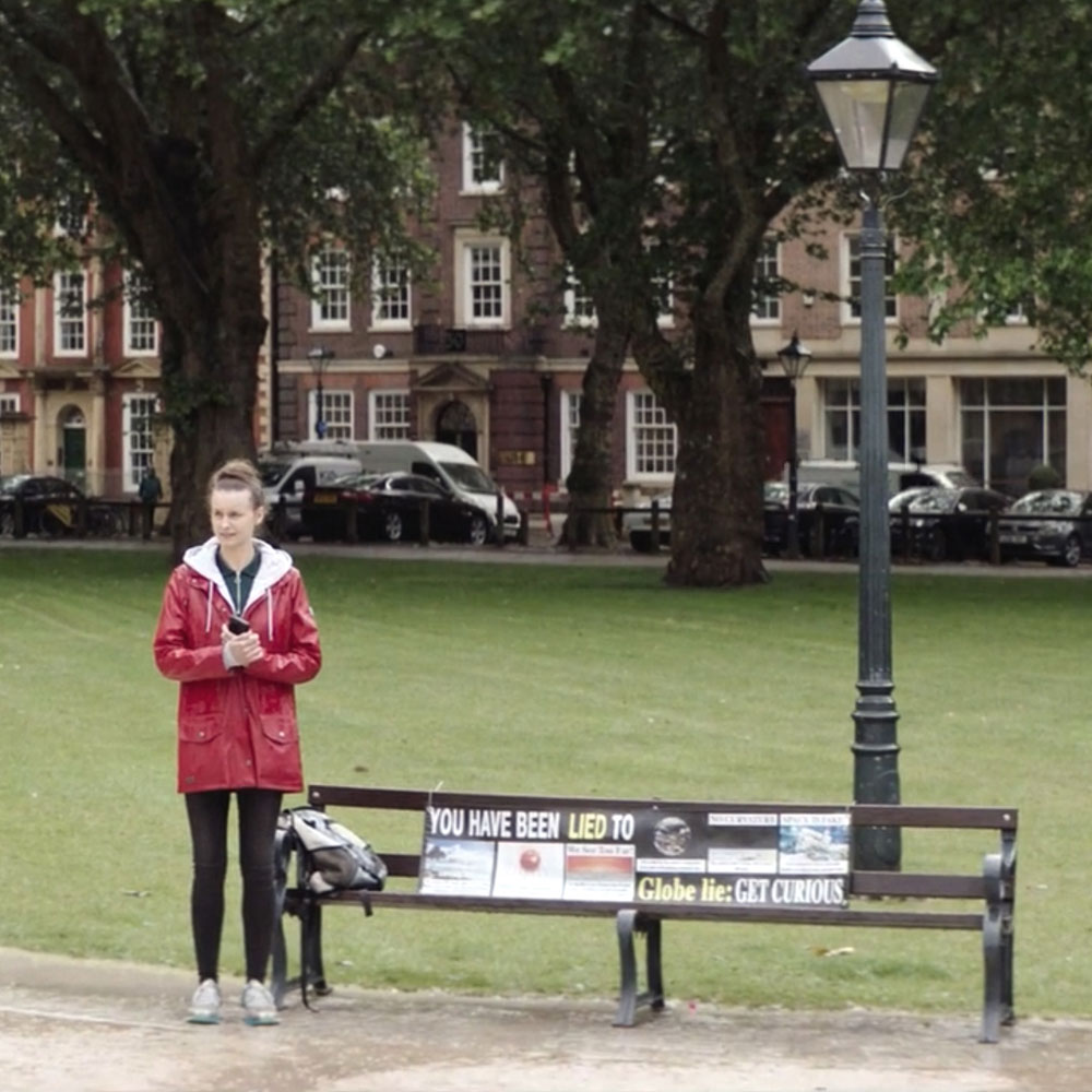 A woman in a red coat stands alone at a bench in a park