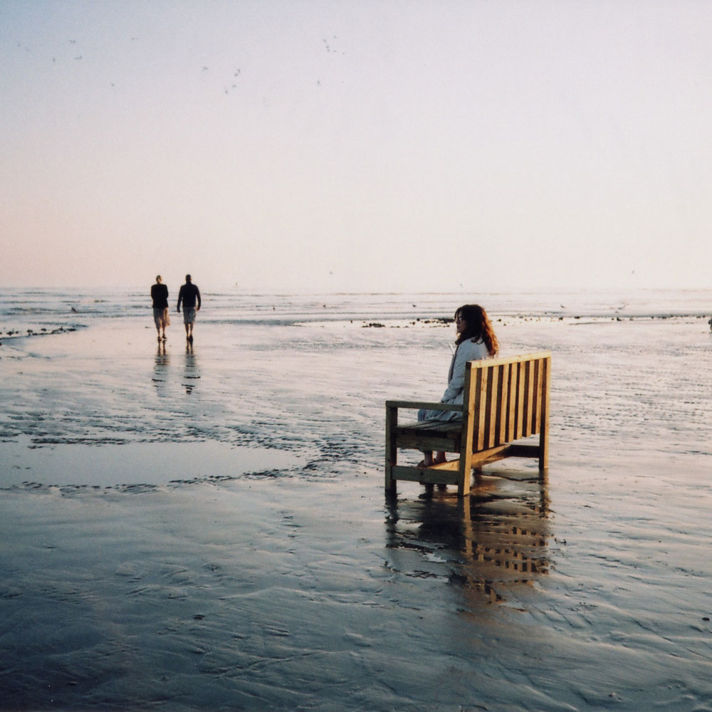 A film still sees a woman sitting alone on a bench on a beach. Two men walk in the distance.