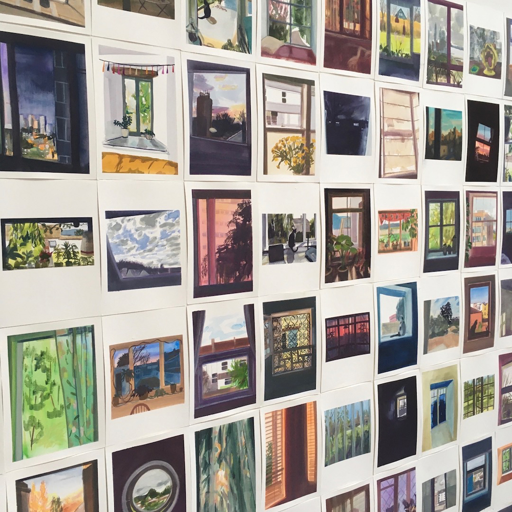 A photograph of around 25 framed photographs of windows hanging on a white wall