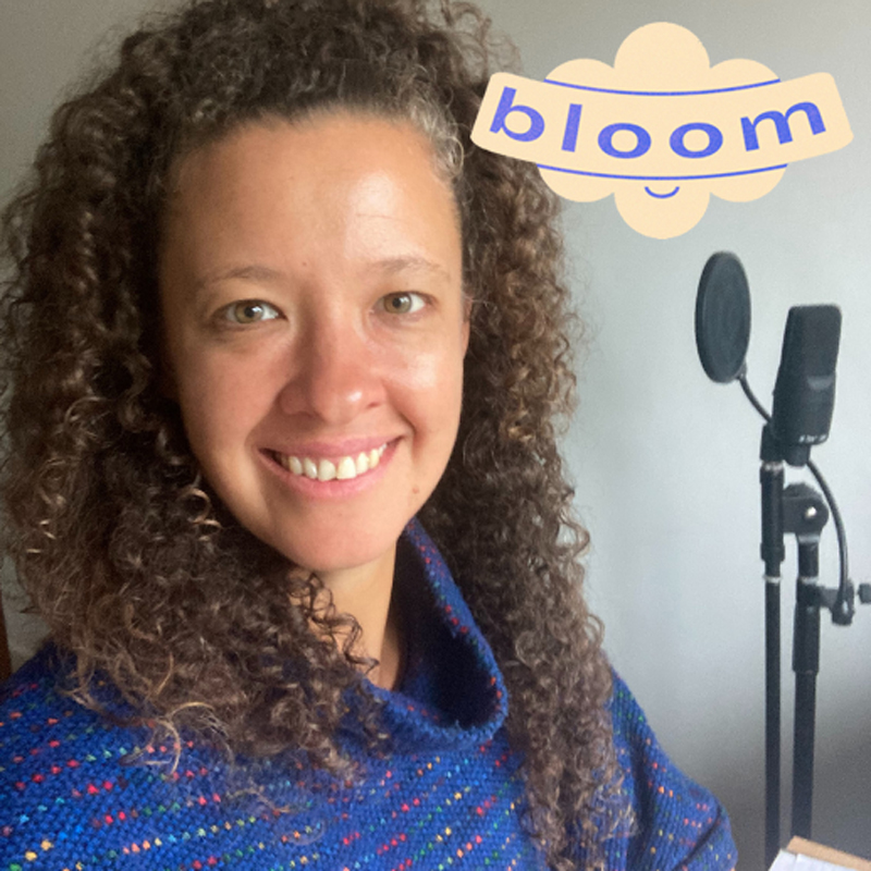 an image of choir leader fran andré smiling at the camera with a microphone in the background. Text reads 'Bloom'