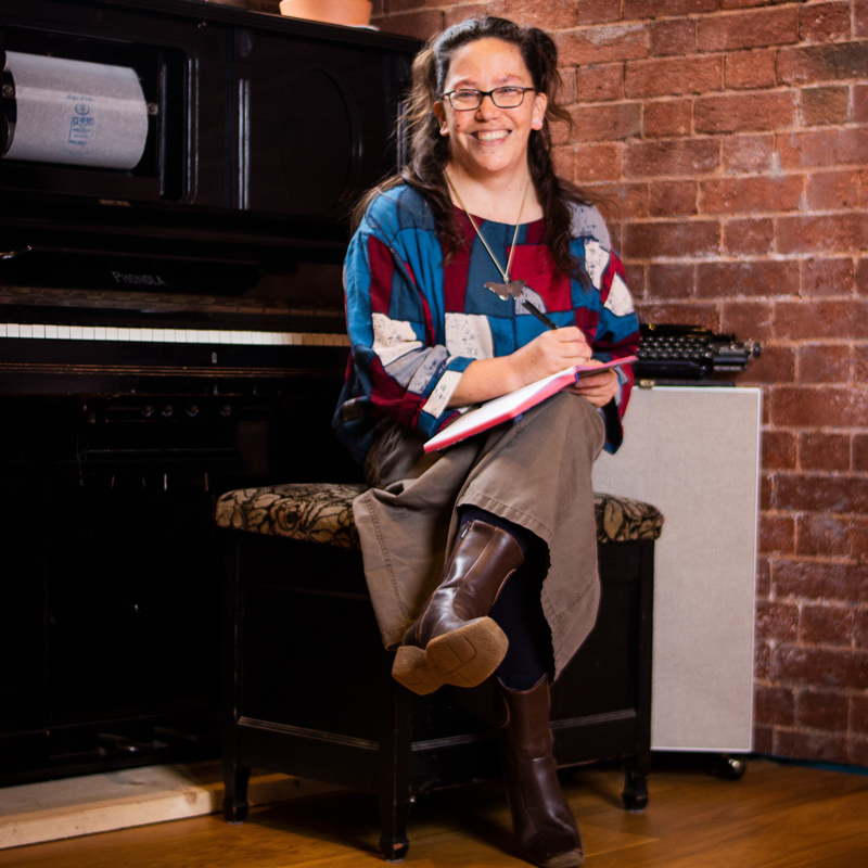 Poet harula ladd sits on a piano stool, smiling at the camera holding a notebook.