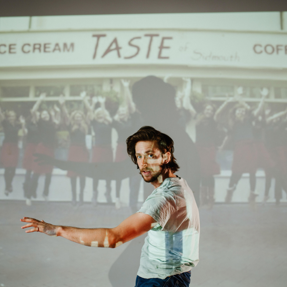 Performer Lewys Holt stands in front of a projector, wearing a white tshirt and looking at the camera.