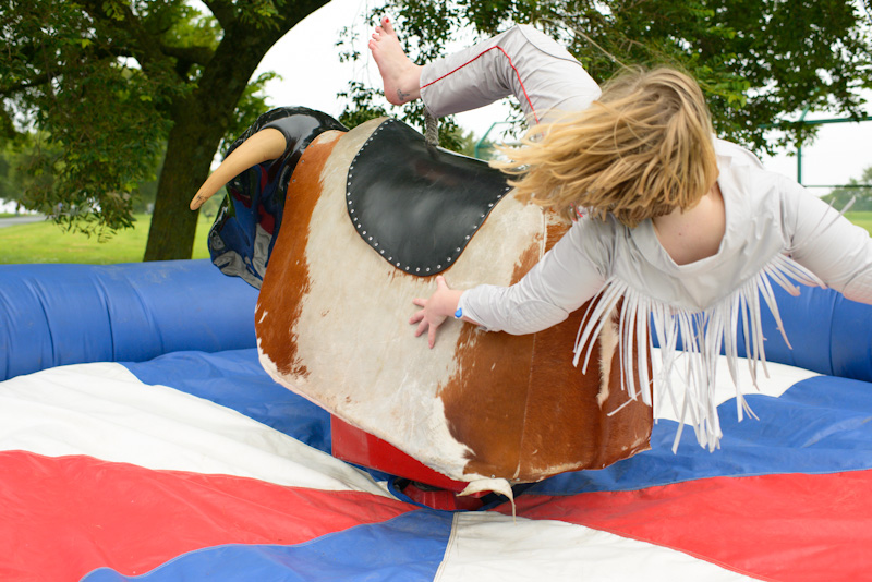 A photograph of Beth Emily Richards falling off of a mechanical bull.