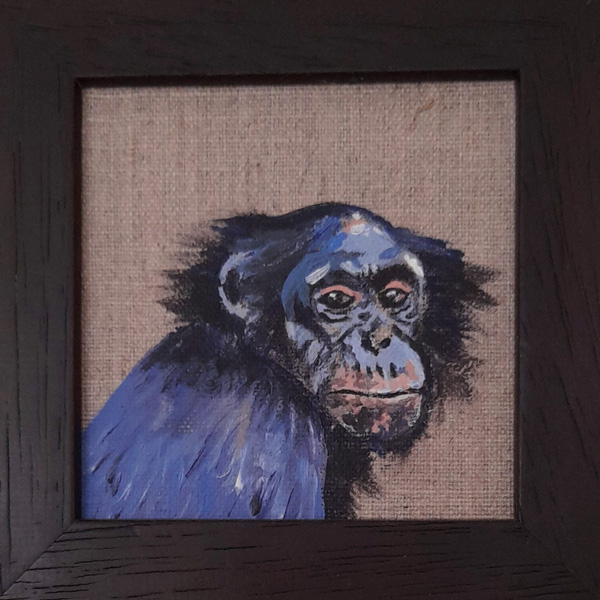 A painted monkey looks out of a wooden frame.