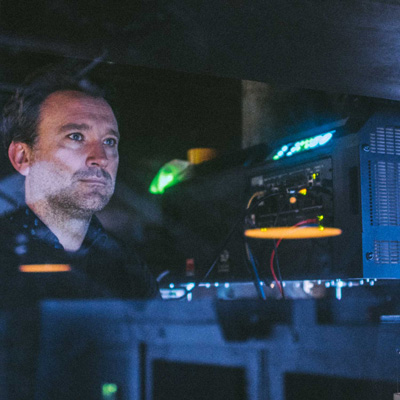 A photographer of Jonas Hawkins in the dmly lit projection box at Exeter Phoenix