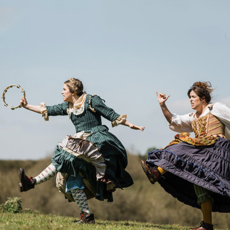 Two female performers running across a field under a cloudless sky. The one in front wears a green dress and waves a tambourine. The second performer wears a gold coloured top and a purple skirt.